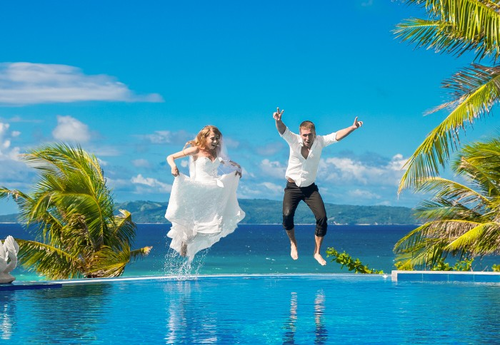 Married couple jumping into pool